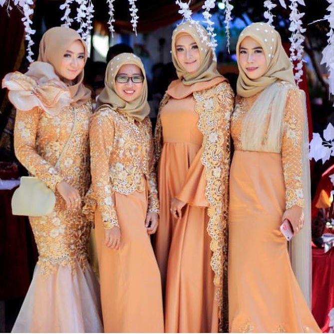 Kebaya Muslim Modern Berbahan Brokat Dan Satin Warna Oranye Dengan Jilbab Warna Coklat Susu.